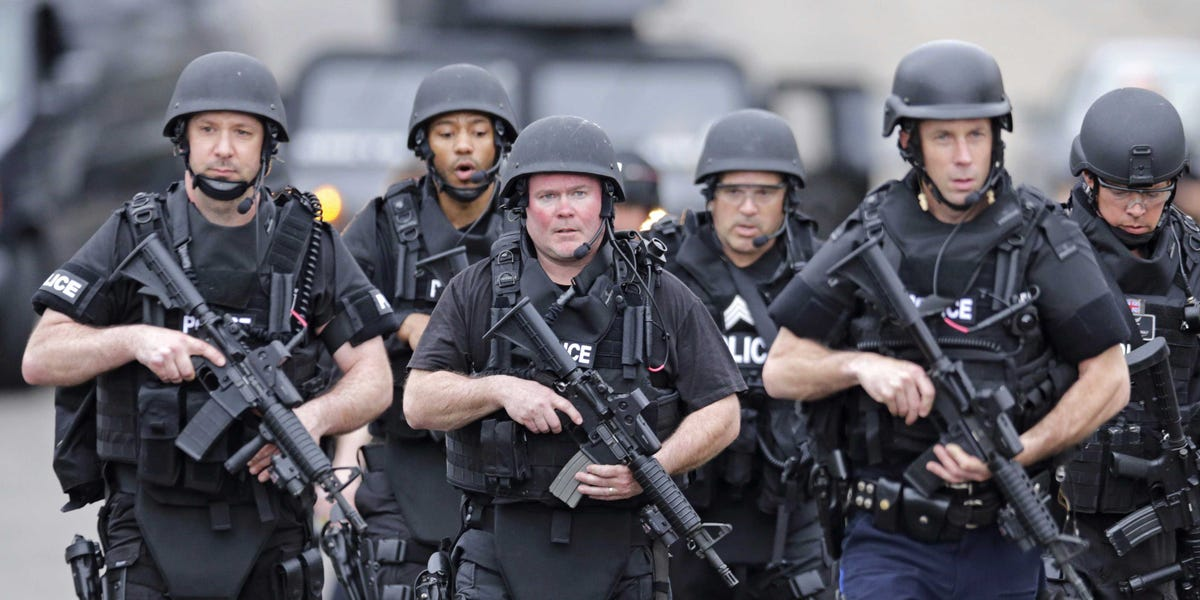 Police carrying assault weapons.