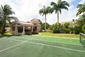 Tennis court with gazebo and pool just beyond