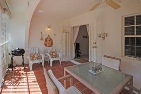 Enclosed sitting and dining terrace leads to garden
