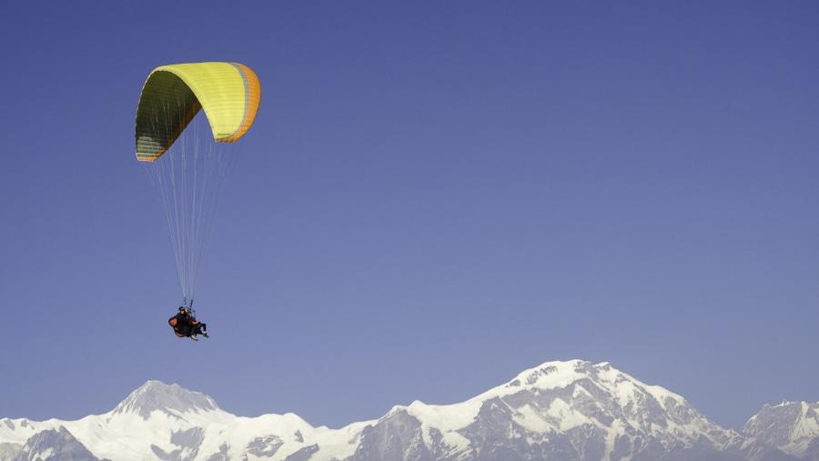 Paragliding over the Sarangkot village and Annapurna Mountain range on background