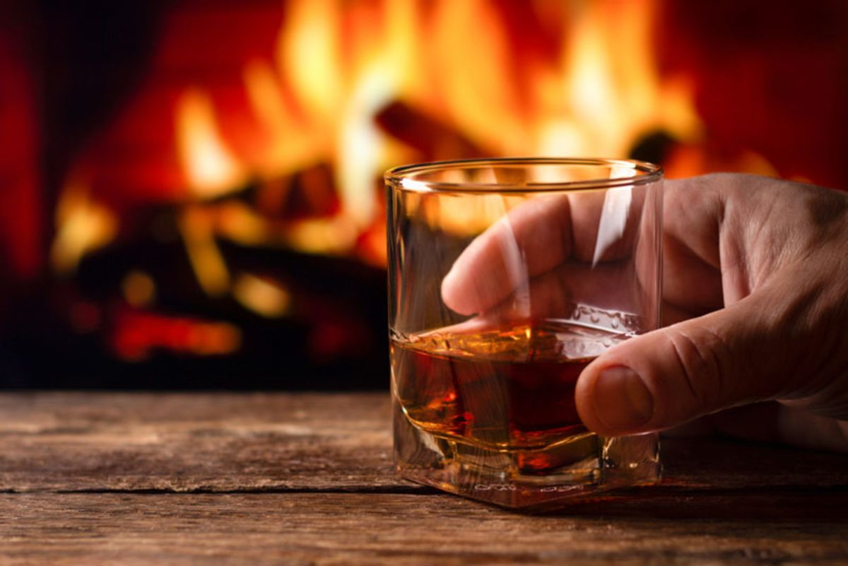 close-up-of-man-holding-a-glass-of-brandy-with-fireplace-in-background