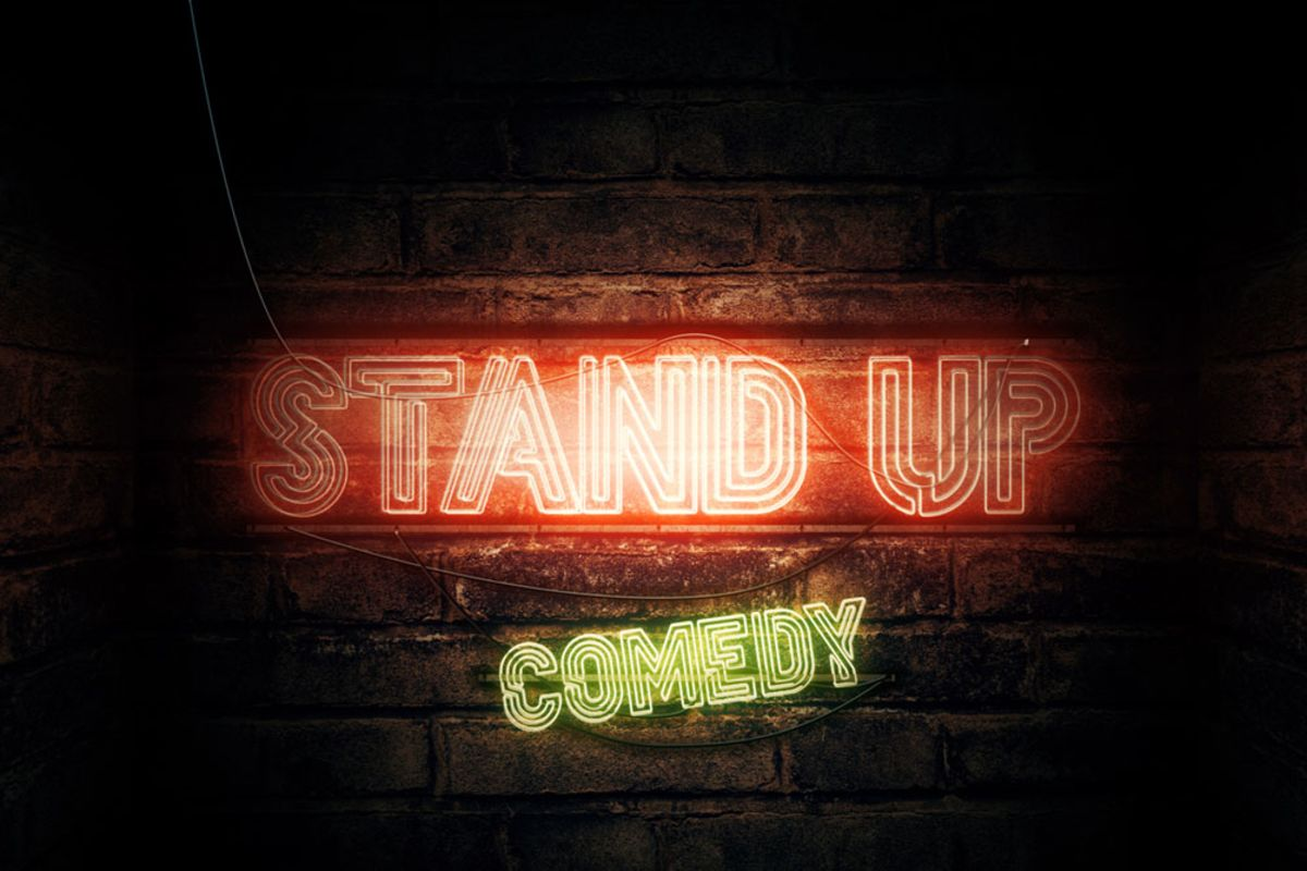 bright-sign-of-stand-up-comedy-in-front-on-brick-wall