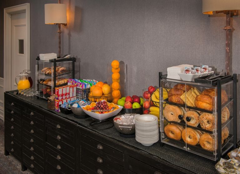 An assortment of pastries, yogurt, and fruit on a counter along the right wall of the lounge.