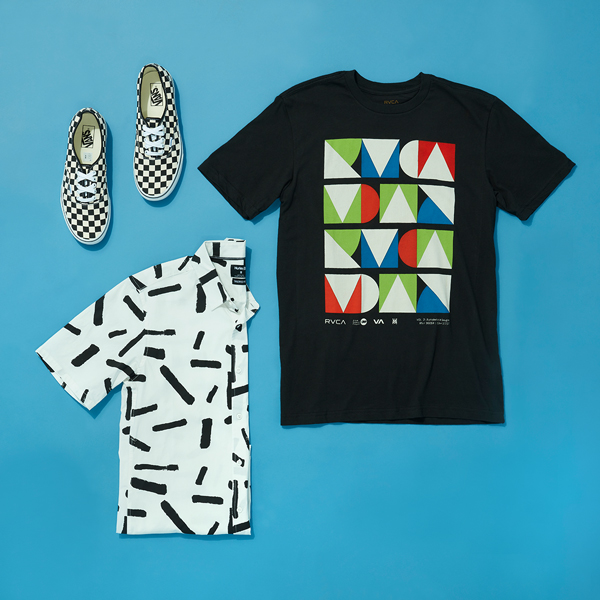 Checkered Vans sneakers paired with a folded collared shirt and black t-shirt printed with geometric designs laid flat on a blue background.
