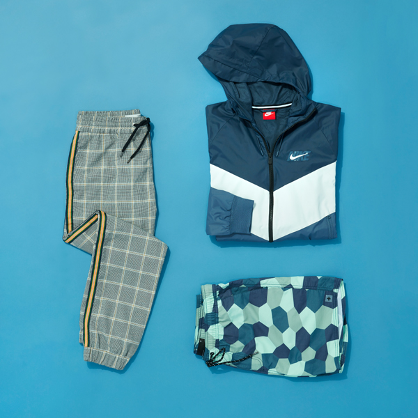 Summer active wear printed with geometric patterns folded and laid flat on a blue background.