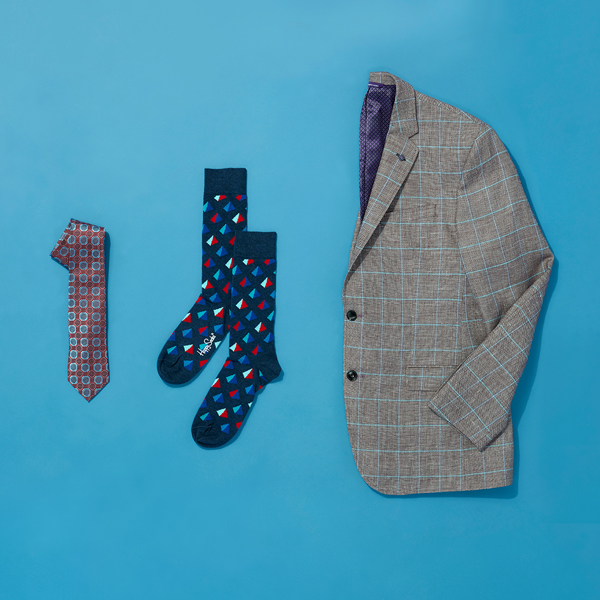 Tie, socks and a dress jacket featuring geometric designs folded neatly on a blue background.