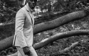 Male model in suit in landscape, black and white image.