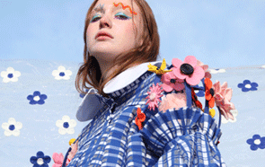Model in blue check dress with flower embellishment against blue background.