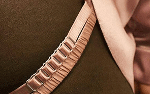 Details of satin pink underwear and suspenders on a body.
