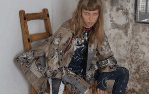 Model sitting on a chair wearing fringed and embroidered vest and trousers against exposed brick wall