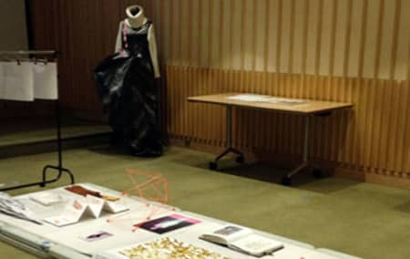 Sketch books on table and mannequin with black and sliver striped dress in background.