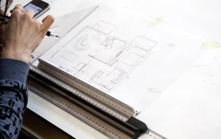 Student drawing a floor plan during Introduction to Interior Design - Plus. Photograph: Spine Photographic.