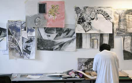 Student with work on the wall during a Portfolio Preparation short course.