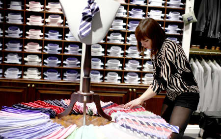 A female student organises a display of ties in the Hackett store.