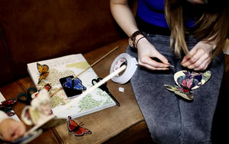A student makes paper butterflies.