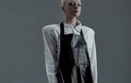 Model in white shirt with shoulder pads and black apron.