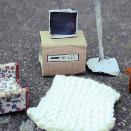 Two miniature chairs and paper television next to a lampshade made of paper.