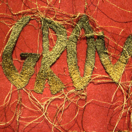 Gold stitched writing on red material background