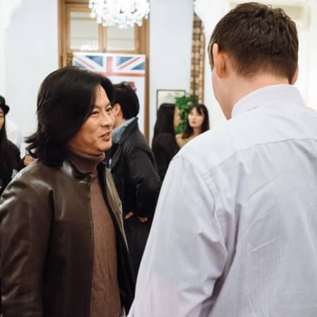 Image of two people talking at UAL alumni event in Seoul, Korea