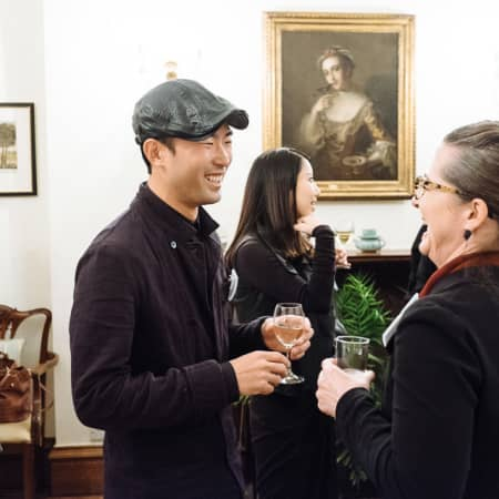 Two people laughing at UAL alumni event in Korea