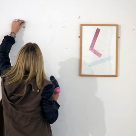 Short course student hanging a framed painting in Art Handling and Installation. Photograph: Jasmin Woolley-Butler.