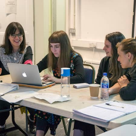 Students gathered around laptop for a lecture during Curating Contemporary Art. Photograph: Jasmin Woolley-Butler.