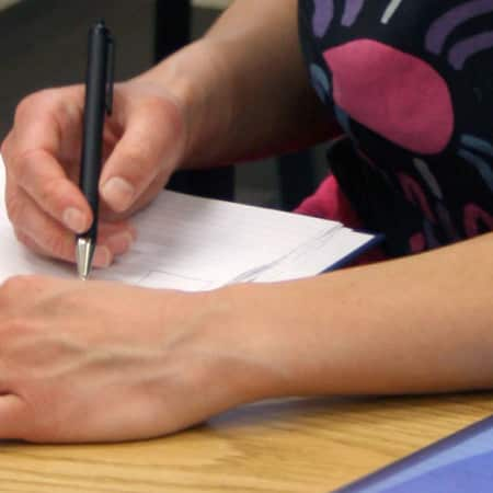 Student working at a desk during a business course.