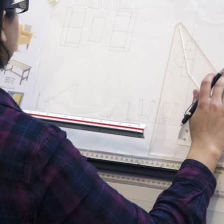 Student hand drawing a technical plan during a short course.