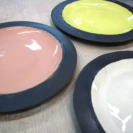 Three plates with coloured glazes made during a ceramics short course at chelsea college of arts.