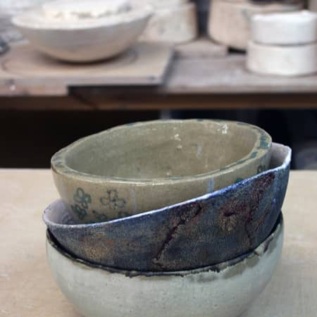A stack of hand built ceramic bowls made by short course students.