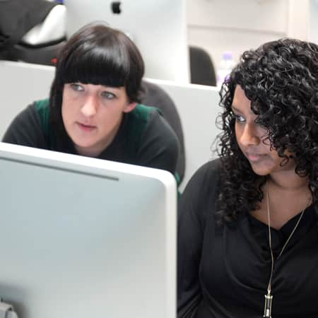 Student and tutor discussing interactive work at a computer screen during a digital design course