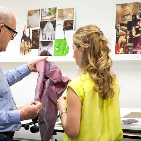 Interior Decoration tutor in discussion with a student about fabric selection.