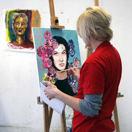 Short Course student at an easel painting an oil painting.