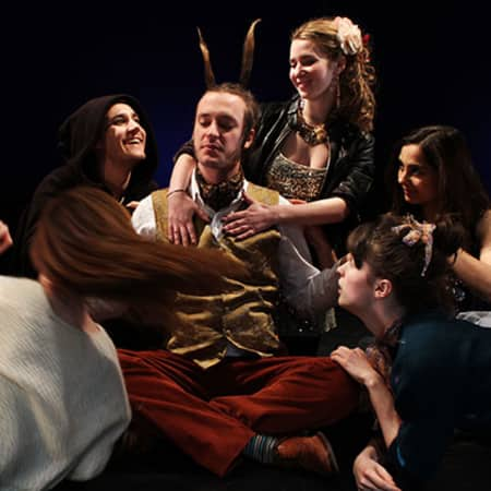 Man with feathers in his hair surrounded by women, Midsummer Night's Dream performance, MA Acting, CSM, 2012.