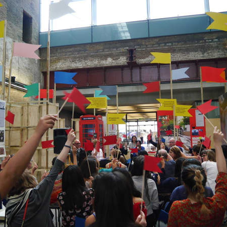 Images of a crowd of people holding up brightly coloured flags in the Crossing at Central Saint Martins