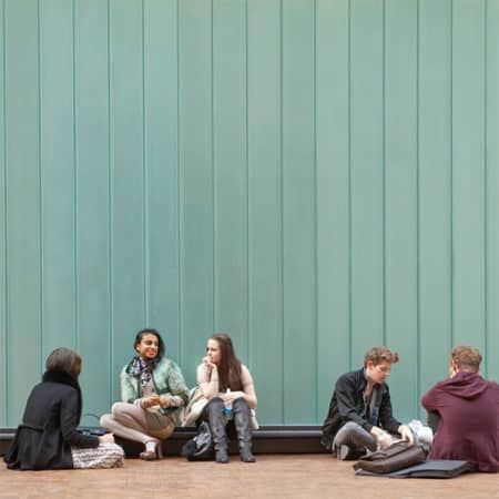Image of students sitting inside the Central Saint Martins building