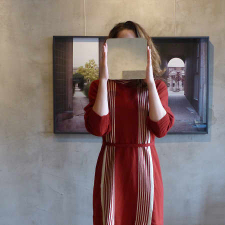 A film still showing a person stood in front of a painting and holding another smaller painting over their face.