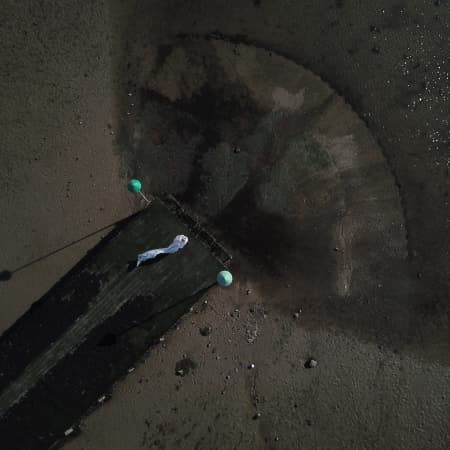 Birds-eye view photograph of a person lying in the middle of an abandoned pier.
