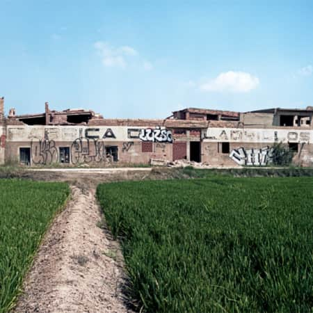 Photograph of a brick factory in Cullera, Spain. View of a brick wall covered in graffiti, against a bright blue sky.
