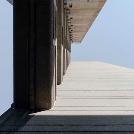 Photography of abstracted view of concrete, Brutalist building with blue sky background.