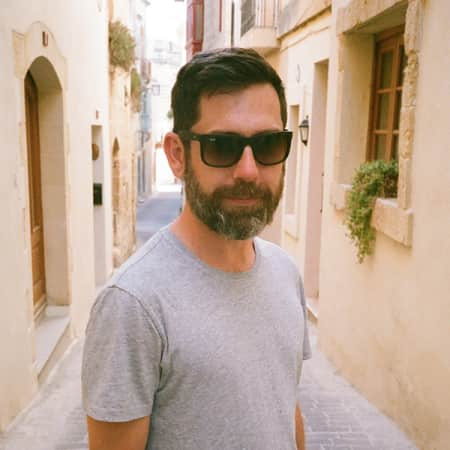 Photograph of Matt Thompson, alumni of Graduate Diploma Photography at London College of Communication. Matt is standing on a street, looking towards the camera and wearing a grey t-shirt and a pair of sunglasses.