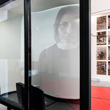 Works in the exhibition Capital City at LCC. In the foreground a transparent screen with a face projected onto it, in the background works on the wall.