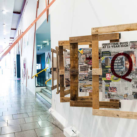 Exhibition view of Capital City at Elephant and Castle. Featuring W11 1TQ – a work made up of a montage of newspapers with the postcode spelt in large red type across each of the six pages.