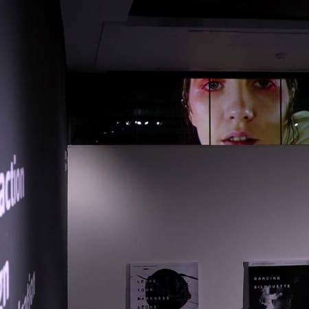 Photo showing multiple pieces of work at the MA Interaction Design Communication, Degree Show 2017, including an image of woman's face imposed along a row of windows.