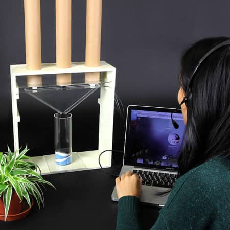A student with a headset and mouthpiece, looking at a laptop. In front of her is a contraption including three tubes which funnel into a glass container, next to this is a plant. The background is black.