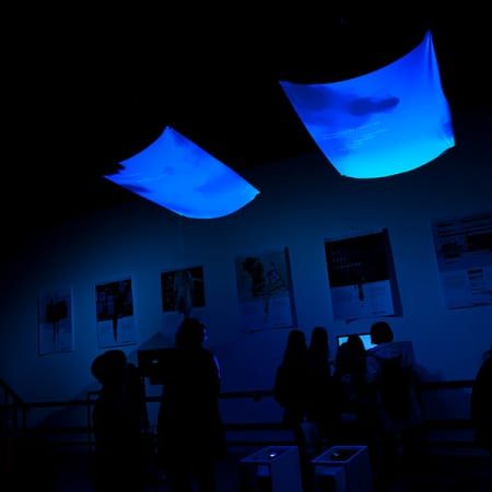 Two fluorescent squares of blue light draped from the ceiling. Claire Alexis's work as part of the MA Interaction Design Communication Degree Show 2017