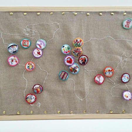 A still from a video, showing a fabric map of the world with embroidered countries, decorated with colourful fabric buttons attached