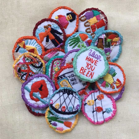 Still from a video, showing a pile of colourful fabric badges with images of people and objects sewn onto them.