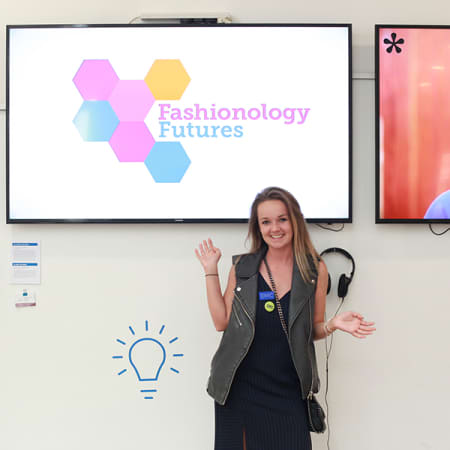 Student standing in front of a screen that reads 'Fashionology Futures' during the Design School Degree Show 2017.