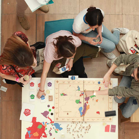 Students sitting around a table, interacting with a colourful wooden map of the world.